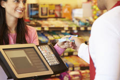 Клиент оплачивая для ходить по магазинам на проверке с карточкой стоковое фото