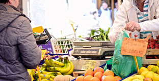 Клиент покупая здоровую еду на местном рынке Стоковые Фото