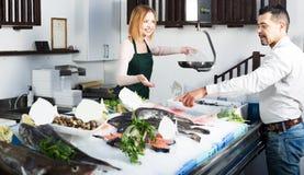 Клиент порции продавца в рыбозаводе Стоковые Изображения RF