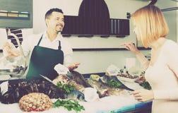 Клиент порции продавца в рыбозаводе Стоковые Изображения