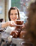 Клиент принимая кофе от официантки в кафе стоковые фотографии rf