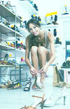 Клиент пробуя на выбранных ботинках Стоковая Фотография