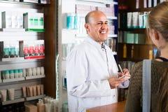 Клиент сервировки аптекаря в фармации Стоковые Фото