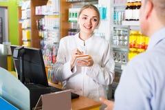 Клиент сервировки аптекаря в фармации Стоковое фото RF