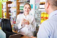 Клиент сервировки аптекаря в фармации Стоковая Фотография