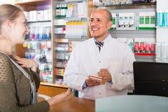 Клиент сервировки аптекаря в фармации Стоковые Фотографии RF