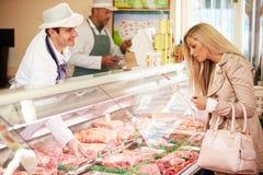 Клиент сервировки мясника в магазине Стоковые Изображения