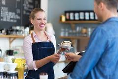 Клиент сервировки официантки на кофейне стоковое фото rf