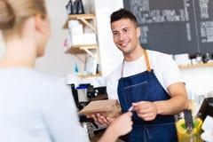 Клиент сервировки Barista в кофейне стоковые фотографии rf