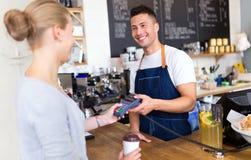 Клиент сервировки Barista в кофейне стоковое фото rf