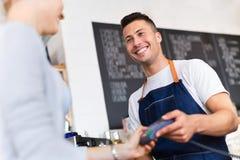 Клиент сервировки Barista в кофейне стоковое изображение