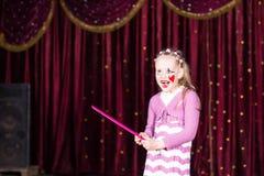 Клоун девушки нося составляет держать большой розовый гребень Стоковое Изображение