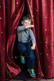 Клоун мальчика скача через занавесы этапа Стоковое Изображение RF