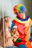 Клоун приглашает маленькую девочку съесть именниный пирог Стоковая Фотография RF