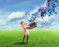 Клоун раскрывает чемодан который вытекает бабочки Стоковые Изображения RF