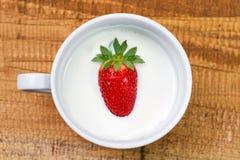 Клубника в молоко чашка с молоком и клубникой на деревянной предпосылке Стоковое Фото