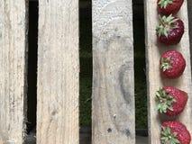 Клубника, лежа в ряд вдоль правильной позиции рамки, на фоне деревянных доск Стоковое фото RF