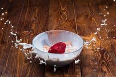 Клубника падая в шар с молоком и хлопьями Стоковая Фотография RF