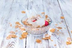 Клубника падая в шар с молоком и хлопьями Стоковая Фотография