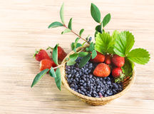 Клубника ягод красная зрелая, и голубой каприфолий Дальний восток в плетеной корзине на таблице Стоковое Фото