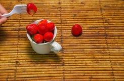 Клубники в чашке, предпосылке ротанга, отборном фокусе на strawberri Стоковая Фотография RF