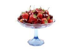 Клубники и вишни в стеклянной стойке изолированной на белой предпосылке Стоковые Фотографии RF