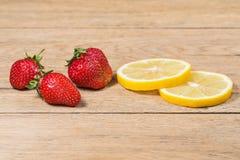 Клубники и куски лимона на таблице Стоковое Изображение RF