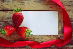 Клубники, красная лента сатинировки и пустая бумажная бирка Стоковые Изображения