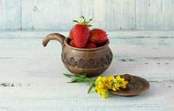 Клубники красные, зрелые лож в коричневом глиняном горшке с ручкой с малыми желтыми цветками на голубой деревянной предпосылке Стоковая Фотография RF