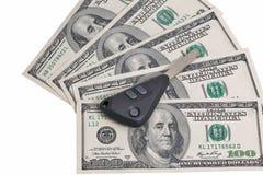 Ключи автомобиля на 100 изолированных предпосылках долларовых банкнот Стоковые Фотографии RF