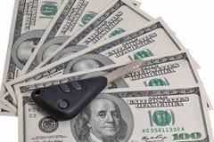 Ключи автомобиля на 100 изолированных предпосылках долларовых банкнот Стоковое Изображение