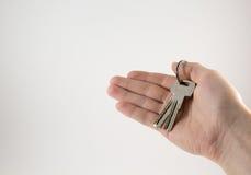 Ключи в руке на белой предпосылке стоковое изображение