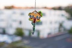 Ключ в форме дома в руке на белой предпосылке Стоковая Фотография
