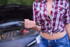 Ключ удерживания женщины для того чтобы разрешить проблему с сломленным автомобилем Стоковая Фотография