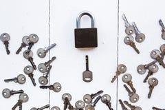 Ключ для всех замков вокруг ключа на белой деревянной предпосылке Стоковое Фото