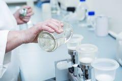 Лаборатория руки льет воду в plactic чашку Стоковая Фотография