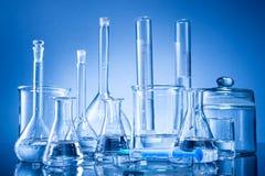 Лабораторное оборудование, бутылки, склянки на голубой предпосылке Стоковая Фотография