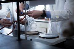 Лабораторное оборудование для выгонки Руки студента/интерна/техника показывая эксперимент Работа в командах для лучшего результат стоковые изображения