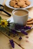 Лаванда рядом с чашкой сметанообразного кофе Стоковая Фотография
