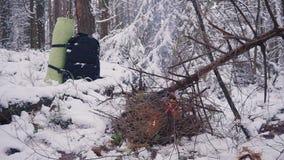 Лагерный костер в лесе зимы и турист укладывают рюкзак акции видеоматериалы