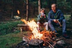 Лагерный костер отца и сына теплый близко на лесе участвовать Стоковая Фотография RF