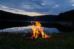 Лагерный костер после захода солнца в горах рядом с озером стоковая фотография