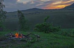 Лагерный костер outdoors на заходе солнца Стоковые Изображения RF