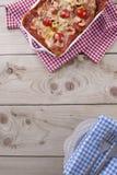 Лазанья испекла в белом листе выпечки, на салфетке в красной клетке и плите с голубой салфеткой на деревянной предпосылке стоковое изображение rf