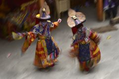 2 лама в традиционных ярких священных одеждах и широких головных уборах выполняют черные шляпы танца на монашеском фестивале Фото Стоковые Фотографии RF