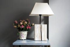 Лампа и цветки на таблице Стоковые Изображения