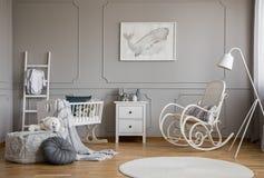 Лампа рядом с кресло-качалкой и половиком в интерьере спальни с вашгердом и плакатом Реальное фото стоковые изображения rf