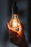 Лампочка при нить, который держат в руке женщины стоковые изображения rf