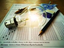 Лампы и канцелярские принадлежности помещенные в листе ответа с воспитательными концепциями стоковое фото rf