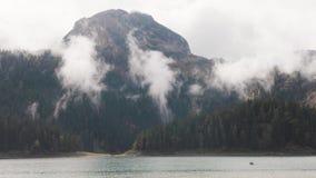 Ландшафт гор и озер с облаками шток Гора с плотным зеленым лесом около голубого озера с облаками нижнего яруса внутри акции видеоматериалы